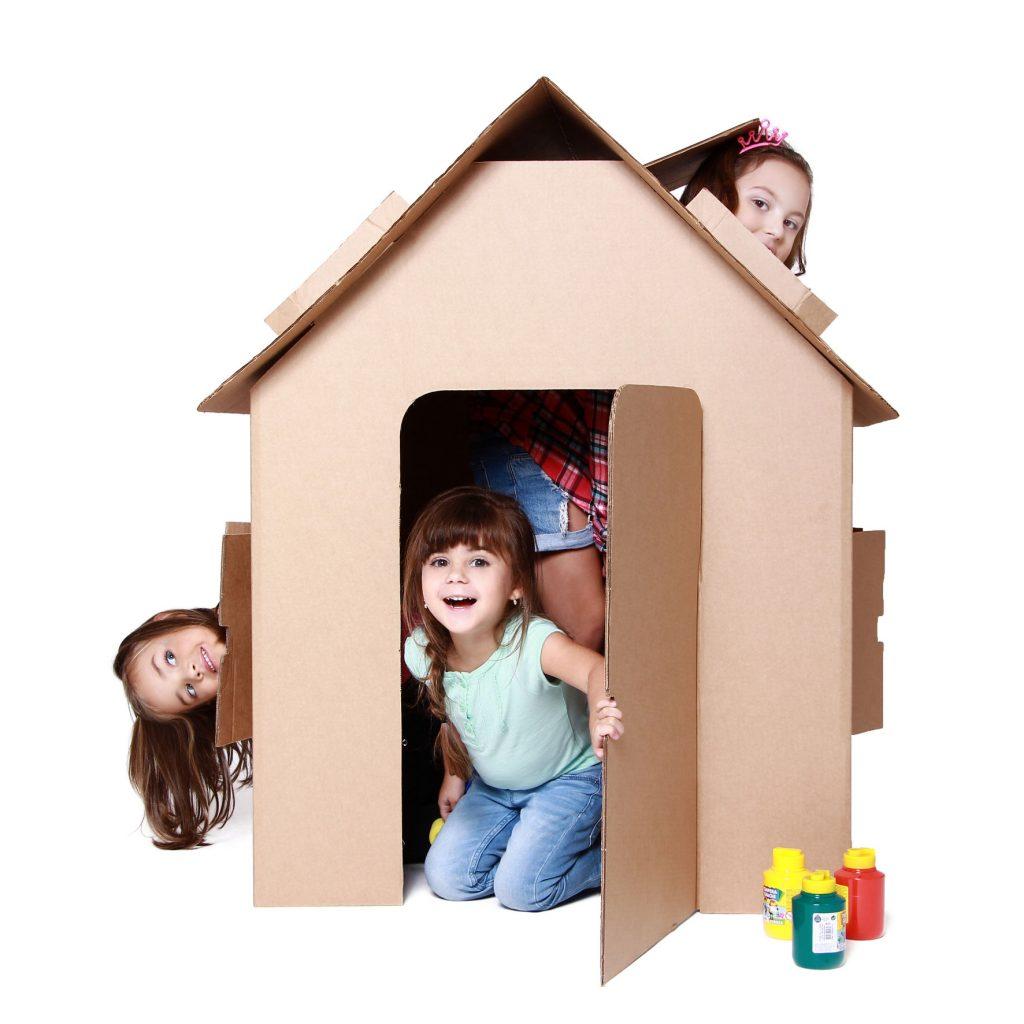 Crianças brincando na casa de papelão