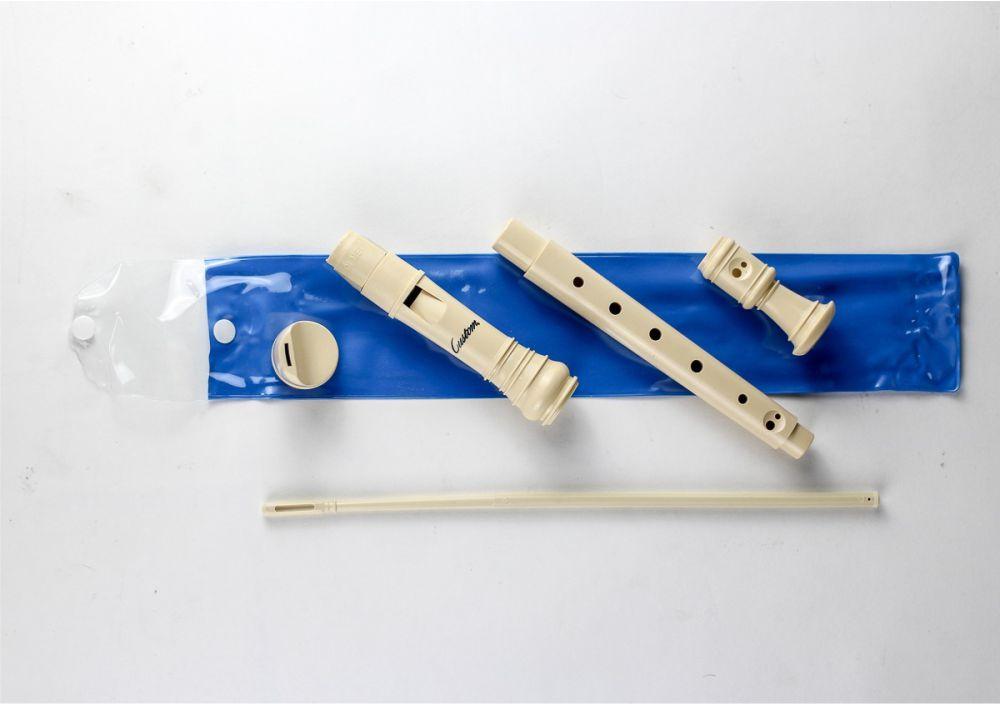 Peças da flauta doce desmontadas em cima da embalagem azul vista de cima